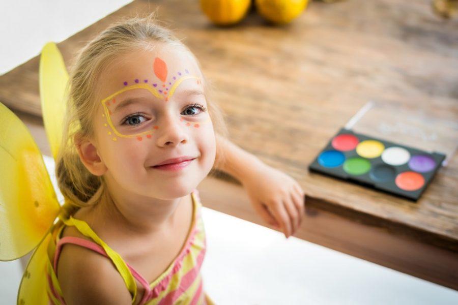 Menina com pinturas faciais no carnaval